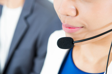 telemarketer: Woman wearing microphone headset as an operator (or telemarketer) - call center and customer service concepts