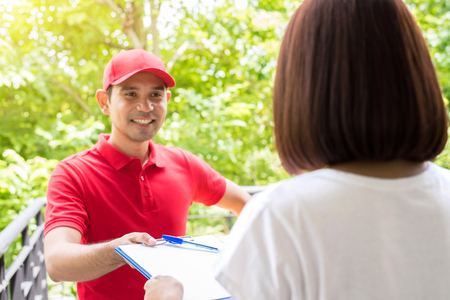 deliverer: Delivery man giving clipboard to a woman to sign Stock Photo