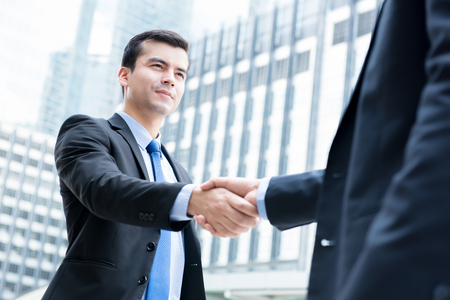 Businessmen making handshake in front of office buildings in the city - greeting, dealing, merger and acquisition concepts