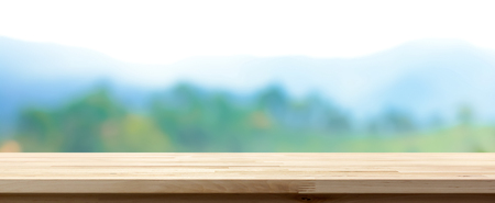 Wood table top on blur green forest and mountain background, panoramic banner - can be used for display or montage your products
