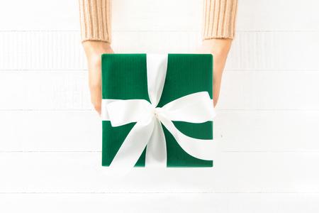 흰색 나무 배경에 녹색 선물 상자를주는 여자 손, 상위 뷰 스톡 콘텐츠