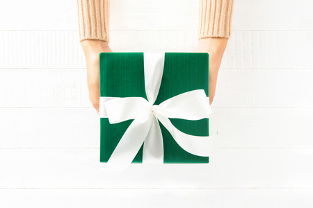 Woman hands giving green gift box on white wood background, top view Imagens