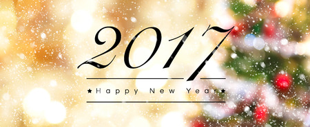 defocus: 2017 Happy New Year text on blur Christmas tree and golden bokeh background with snow effect, panoramic banner Stock Photo