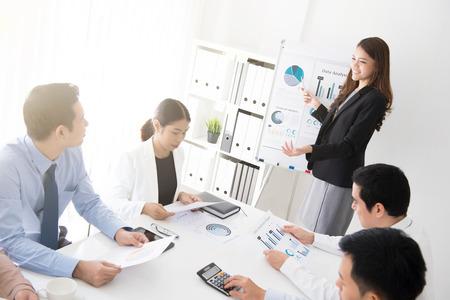 Mujer de negocios asiática presentar su trabajo en la reunión
