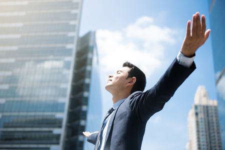 Happy businessman raising his arms, open palms, with face looking up  - empower, success and freedom concepts Foto de archivo