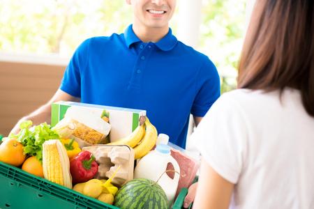 Szállítás ember élelmiszer-szállító egy nő otthon - online bevásárló szolgáltatás fogalmát