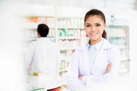 Smiling asian woman pharmacist in pharmacy (chemist shop or drugstore)