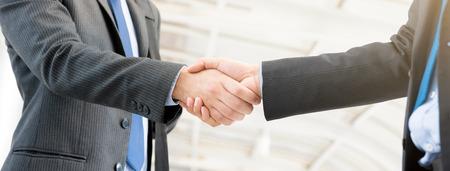 Businessmen making handshake,  panoramic banner Standard-Bild