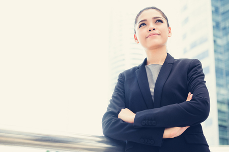 woman business suit: Asian businesswoman standing and crossing her arms in blur building background, vintage tone effect Stock Photo