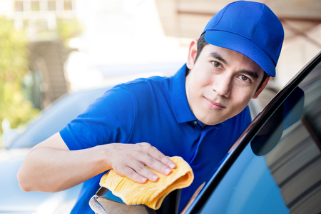 valeting: Auto service staff polishing (cleaning) car with microfiber cloth, car detailing or valeting concept