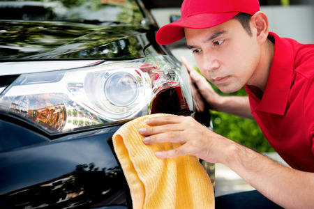 valeting: Auto service staff in red uniform cleaning car with microfiber cloth - car detailing and valeting concepts Stock Photo