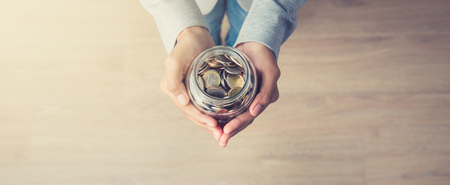 investment concept: Young woman hands holding glass jar with money (coins) inside - panoramic banner background, top view, with copy space