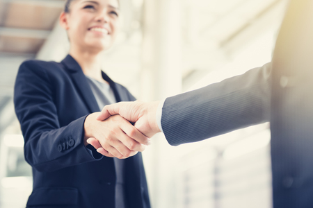 Smiling young businesswoman making handshake with a businessman