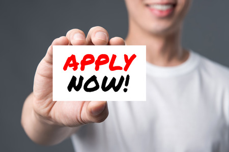 APPLY NOW! message on the card shown by a man Stock Photo