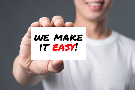 WE MAKE IT EASY! message on the card shown by a man Stock Photo