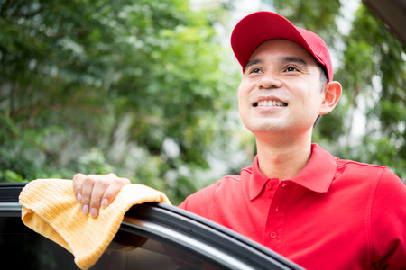 valeting: Smiling auto service staff thinking(daydreaming) while cleaning car door Stock Photo