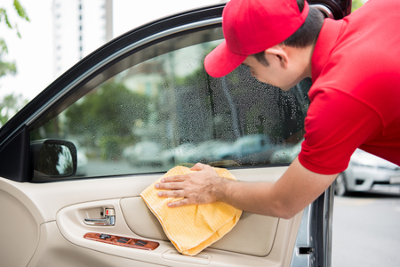 valeting: A man cleaning car door interior panel with microfiber cloth - auto cleaning service concept
