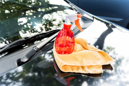 Cleaning equipments, spray bottle and microfiber cloth, on car bonnet