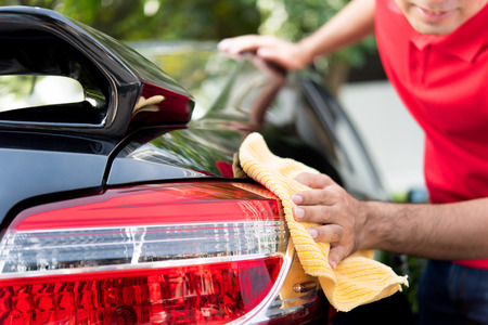valeting: A man cleaning car tail light - auto service, detailing and valeting concept