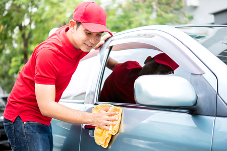 valeting: A man in red uniform cleaning car - auto service concept