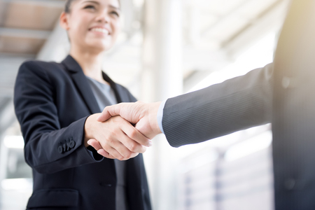 Businesswoman faisant poignée de main avec un homme d'affaires Accueil des voyageurs, traitant, fusions et acquisitions concepts