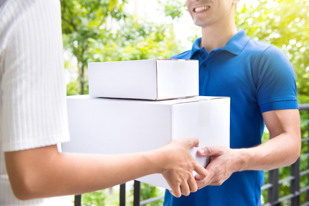 deliverer: Smiling delivery man deliver postal packages to a woman - courier and delivery service concepts