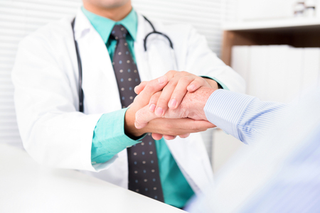 Doctor holding senior male patient hand with care Stock Photo