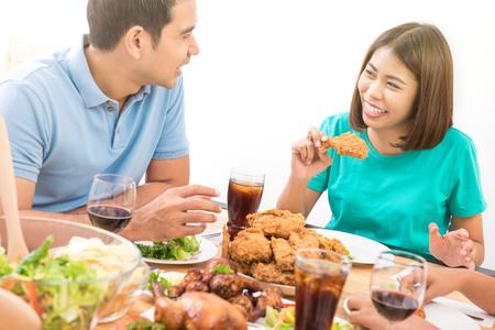Happy Asian couple smiling to each other while eating dinner Banco de Imagens