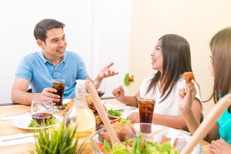 Personas disfrutando de comer y tener conversación en la mesa de comedor Foto de archivo - 79953629