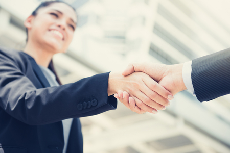 Businesswoman making handshake with a businessman - greeting, dealing and partnership concepts Stock Photo