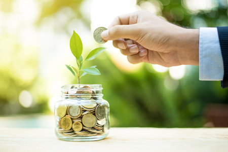 Plant growing from money in the glass jar - financial metaphor,  savings and investment  concept Archivio Fotografico