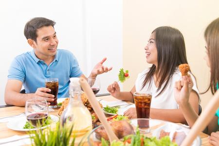 ダイニング テーブルで楽しんで食べていて会話を人々 します。