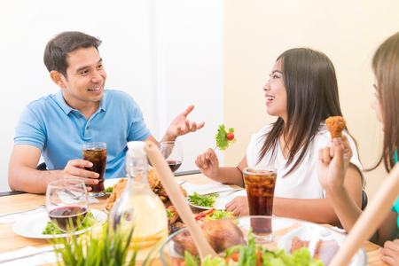 People enjoying eating and having conversation at dining table Imagens