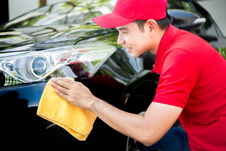 Auto service staff in red uniform cleaning car Stock Photo