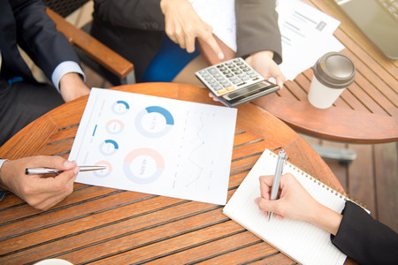 Business people calculating and discussing financial documents on the table in coffee shop Stock Photo