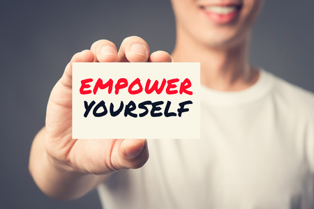 EMPOWER YOURSELF, message on the card shown by a man, vintage tone effect
