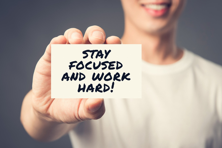 STAY FOCUS AND WORK HARD! message on the card shown by a man, vintage tone effect