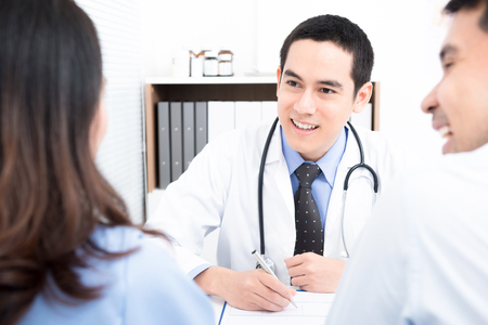 Doctor consulting with young couple patients - family and infertility consultation concepts