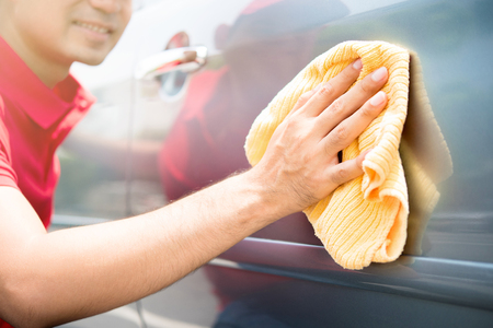 valeting: Auto service staff cleaning car door with microfiber cloth