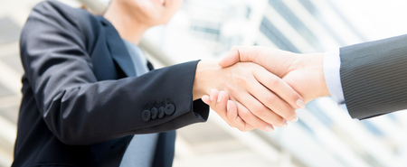 Businesswoman making handshake with a businessman - panoramic banner background