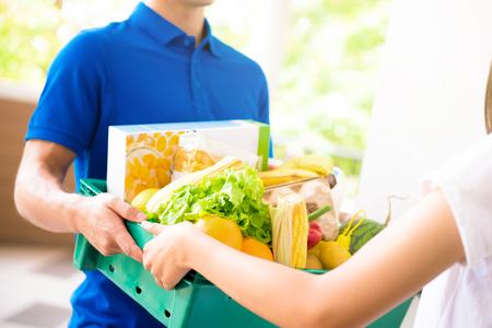 hombre de salida que entrega alimentos a una mujer en su casa - concepto de servicio de compras en línea