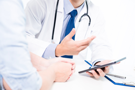 Doctor talking  and explaining treatment to patient by using tablet computer