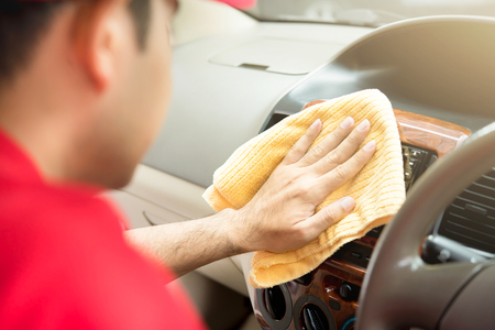 valeting: A man cleaning car interior with microfiber cloth - auto detailing and valeting concept