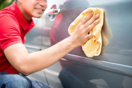 Auto service staff cleaning car door with microfiber cloth