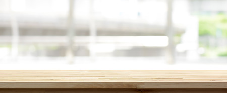 Wood table top on blur kitchen window background, panoramic banner - can be used for display or montage your products (food)