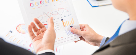 Businessmen discussing and analyzing financial graph document - panoramic banner