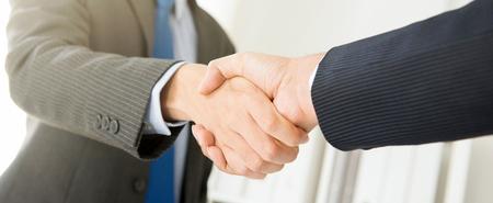 Geschäftsmänner, die Händedruck, panoramische Fahne - Gruß-, Handels-, Fusions- und Erwerbskonzepte machen Standard-Bild