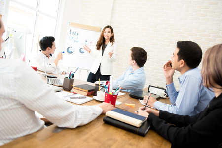 Asian business woman presenting work to mixed race colleagues in the meeting