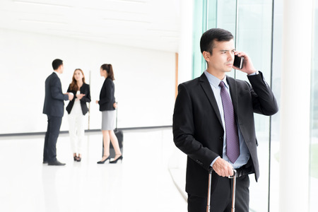 corridors: Traveling businessman calling on smartphone at building hallway (airport terminal)