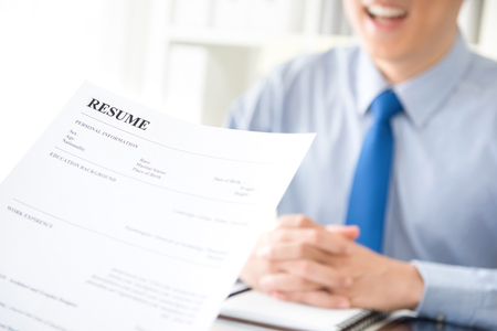 Young businessman submitting resume to employer to review  - job application and interview concepts
